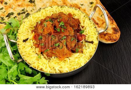 Lamb rogan josh curry meal with pilau rice and naan bread