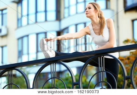 Young woman stretching near handrail on the street