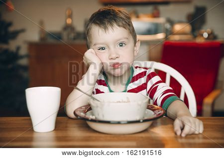 sad boy and a plate of porridge. upset child at the table. the concept of eating disorders. healthy porridge on Christmas morning instead of a festive breakfast