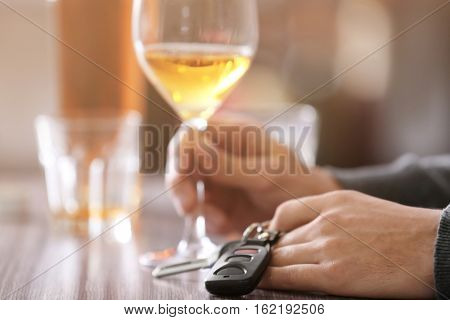Man sitting at table with car key and glass of alcoholic beverage, closeup. Don't drink and drive concept