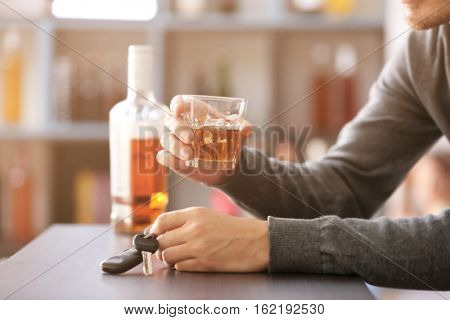 Man sitting in bar with car key and glass of alcoholic beverage. Don't drink and drive concept
