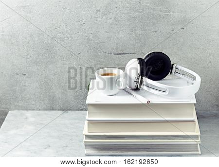 A cup of coffee and headphones on a stack of books