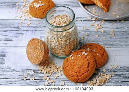 Oatmeal cookies and glass jar with groats on wooden background