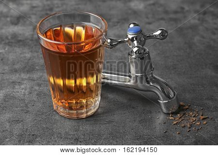 Water shortage concept. Glass of dirty water and tap on grey background