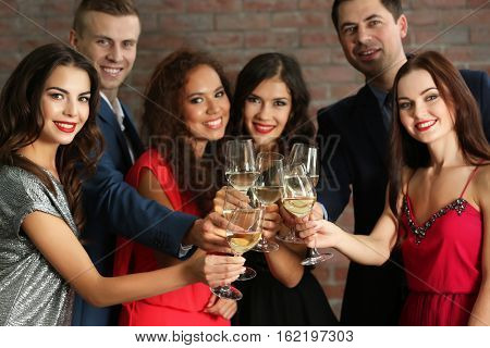 People toasting with glasses of white wine