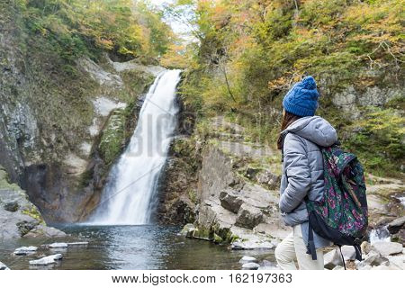 Woman hiker standing forest trail and looking at waterfall