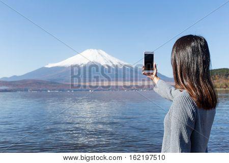 Woman using mobile phone to take photo on Fujisan