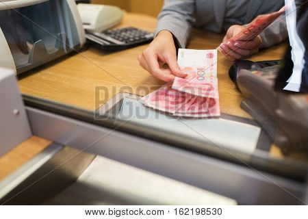 people, withdrawal, saving and finance concept - clerk counting cash money at bank office or currency exchanger