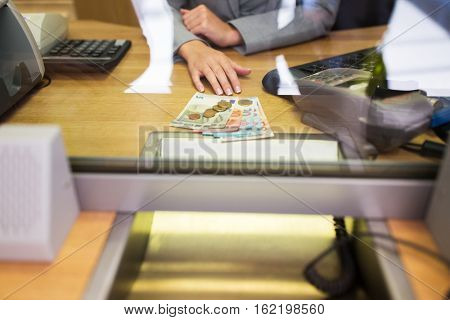 people, saving, currency exchange, withdrawal and finance concept - clerk hands with cash money at bank office