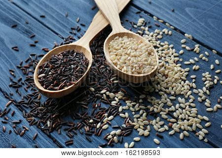 Two types of rice in spoons on wooden background