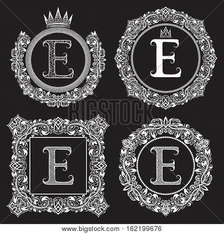 Vintage monograms set of E letter. Heraldic coats of arms in wreaths round and square frames. White symbols on black.