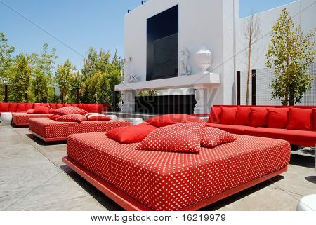 Outdoor lounge area  of nightclub and restauraunt with red chairs and cushions and a fireplace.