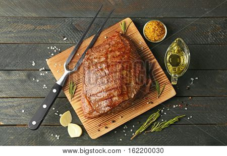 Delicious moist steak on board and grey wooden background