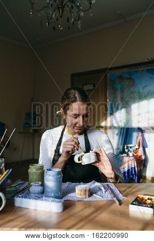 Pretty young woman potter paints a clay cup. Woman working In her pottery studio
