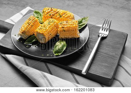 Kitchen board with plate full of cut tasty grilled corncobs on wooden table