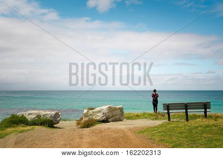 Traveler taking a photo of seascape of Cape Leeuwin along the Indian Ocean Augusta Western Australia .