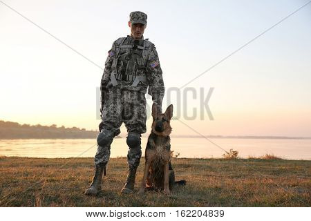 Soldier with german shepherd dog near river at sunset
