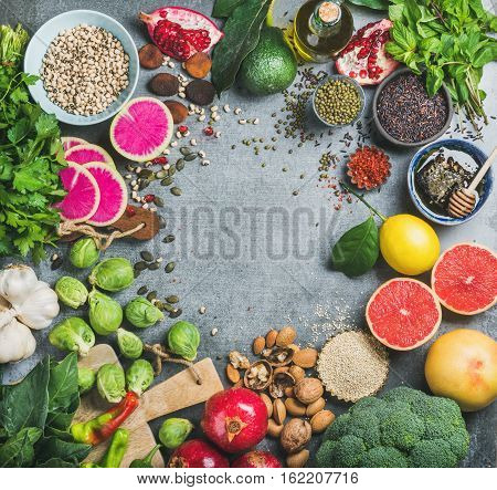Clean eating concept over grey concrete background, top view, copy space. Variety of vegetables, fruit, seeds, cereal, bean, spices, superfood, herbs, condiment for vegan, raw diet or gluten free diet