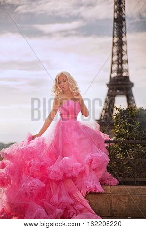 Elegant Parisian woman in pink tutu dress with white roses sitting near the Eiffel tower at Trocadero view point in Paris, France