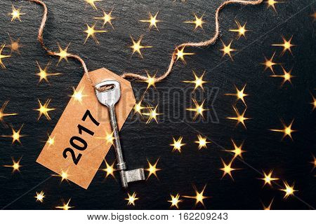 Metal key with 2017 year tag. Festive picture with lightening golden stars.