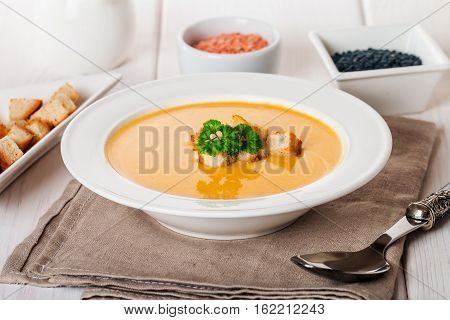 Vegetarian lentil cream soup with croutons, lentil and vegetables on white wooden background
