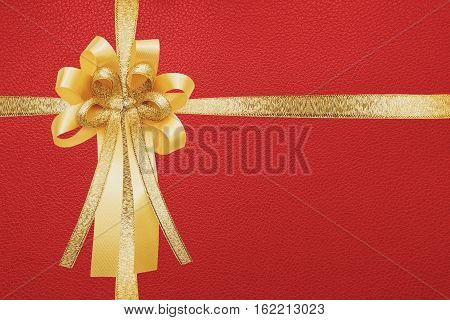 Golden ribbon and bow, wrap on red gift box background