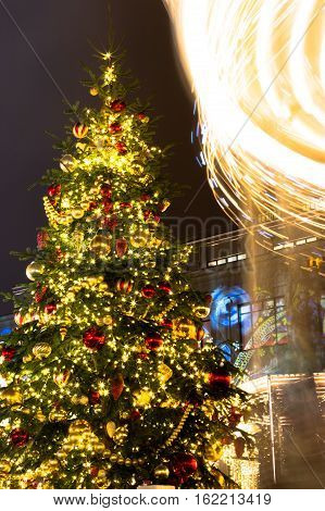 Christmas Fair. Christmas tree and a rotating carousel. Bright illumination. Fair in Moscow. Christmas screensaver. Background for a card.