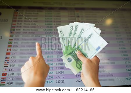 finance, currency conversion and people concept - hands with euro money pointing finger to exchange rates on digital display screen