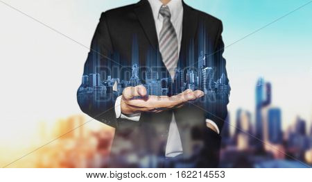 Double exposure businessman holding blue city hologram, with city in sunrise background, real estate business technology concepts