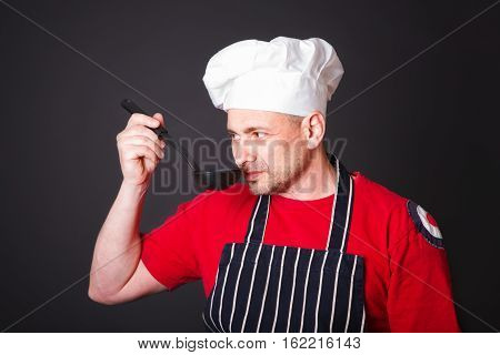 Portrait of a funny cook with a ladle in his hand in the studio on a black background
