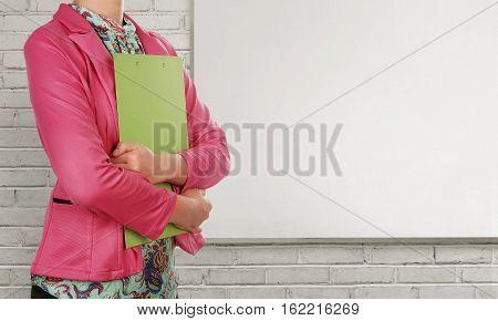 Businesswoman With Clipboard Standing Beside Blank Whiteboard