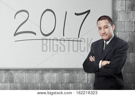 Attractive asian businessman with 2017 written on the whiteboard. New year concept.