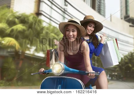 Beautiful Two Asian Woman Riding The Scoote