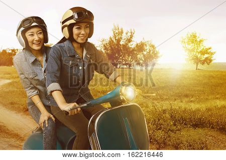 Two Pretty Asian Woman Having Fun Riding The Scooter When Sunset