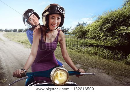 Cheerful Friendship Two Asian Woman Riding The Scoote