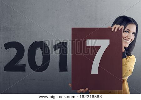 Asian Business Woman Holding Paper With Numbers 7 In The Wall 2017