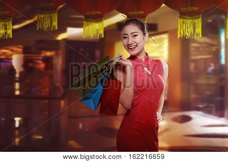 Asian Woman In Cheongsam Dress With Shopping Bag