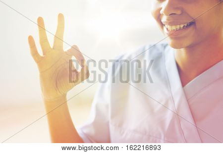 gesture, people and medicine concept - close up of happy african female doctor or nurse showing ok sign at hospital