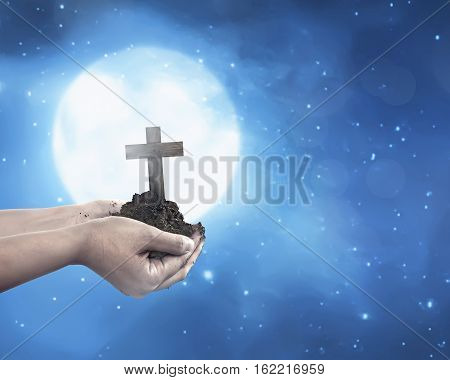 Human Hand Holding Christian Cross With Soil On The Hand