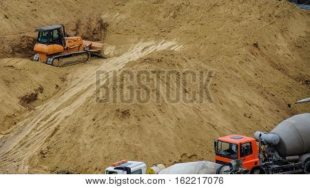 bulldozer is dig in sand preparing ground for new building