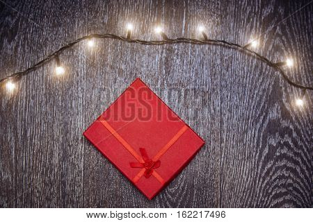 Christmas light and gift box on a hardwood background