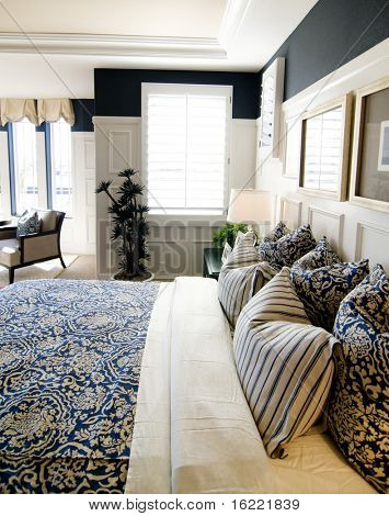 Beautifully designed bedroom interior with white and blue coloring and shutters