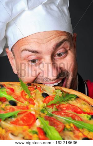 Portrait of happy attractive cook with a pizza in studio an a black background