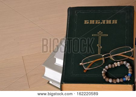 Closed Bible with glasses and a rosary. Russian