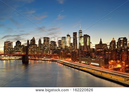 View of Lower Manhattan with Brooklyn Bridge and FDR Drive at sunset.