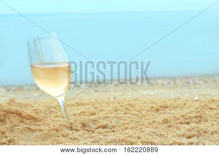 Glass of wine on sand on sea background