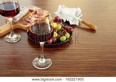 Glasses with red wine, grape, wurst and cheese on wooden background