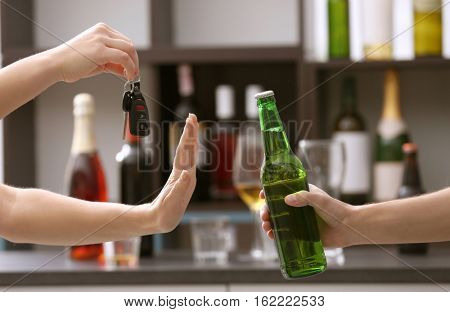 Woman with car key refusing bottle of beer, on blurred background. Don't drink and drive concept