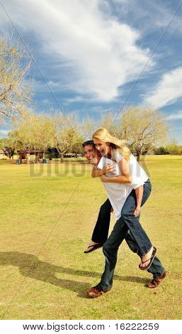 Attractive couple having fun in a park playing piggy back  on a warm spring day.  This image is part of an engagement shoot.