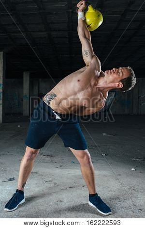 Front view of inclined man holding dumbbell up standing in abandoned building.